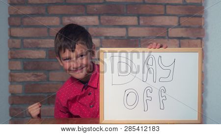 Portrait Little Boy Showing Whiteboard With Handwriting Word Day Off. Child Rejoices Holiday. Preado