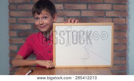 Portrait Little Boy Showing Whiteboard With Handwriting Word Million Dollars. Child Put A Signature.