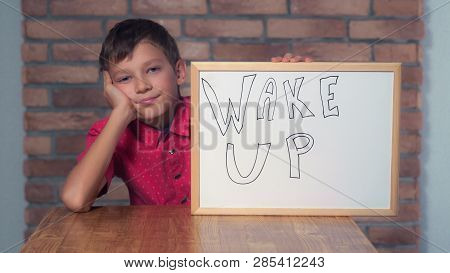Portrait Little Boy Showing Whiteboard With Handwriting Word Wake Up. Child Smiling And Yawns. Pread