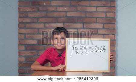 Portrait Little Boy Showing Whiteboard With Handwriting Freedom. Child Smiling Looking At Camera. Pr