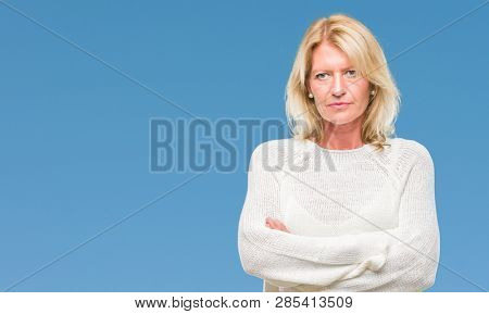Middle age blonde woman wearing winter sweater isolated background skeptic and nervous, disapproving expression on face with crossed arms. Negative person. poster