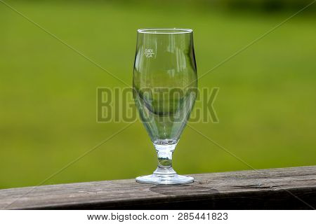 Empty Glass Of Beer On Wooden Table On Green Nature Background. Empty Glass Of Beer On Green Nature