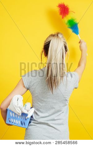 Dust Cleaning. Woman With Feather Duster And Basket Of Cloths On Yellow Background. Backview.