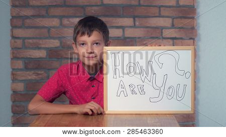Portrait Little Boy Showing Whiteboard With Handwriting Word How Are You. Schoolboy With Asking On H