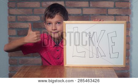 Portrait Little Boy Showing Whiteboard With Handwriting Word Like. Child Shows Hand Gesture Thumbs-u