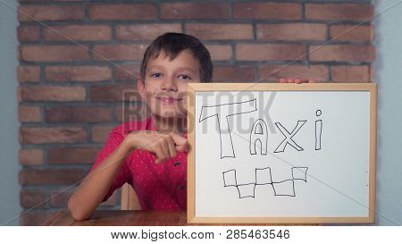 Portrait Little Boy Showing Whiteboard With Handwriting Word Taxi. Child Smiling Looking At Camera.