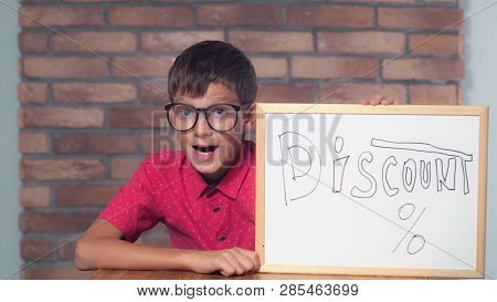 Portrait Little Boy Showing Whiteboard With Handwriting Word Discount. Child With Spectacles On Smar