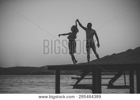 Romance And Love Concept. Silhouette Of Sensual Couple Dancing On Pier With Sunset Above Sea Surface