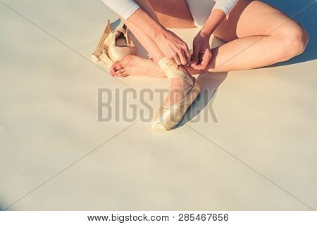 poster of Dancing on pointe. Ballerina shoes. Ballerina legs in white ballet shoes. Lacing ballet slippers. Female feet in pointe shoes. Pointe shoes worn by ballet dancer. Classic dance style. Concert dance performance.