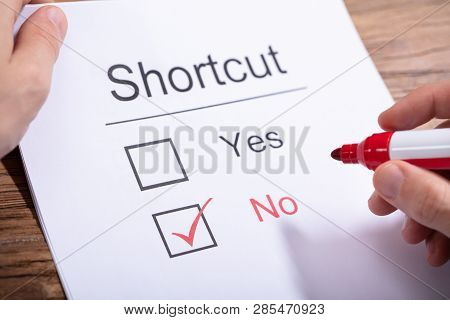 A Person Holding Marker Over Paper With Shortcuts Word Showing Yes And No Option