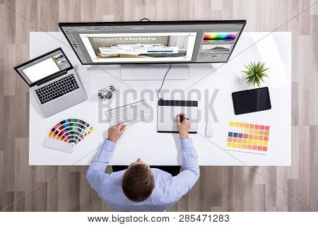 Elevated View Of Male Graphic Designer Working On Graphic Tablet Over White Desk