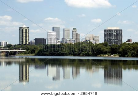 Skyline view of the city of Tulsa Oklahoma with buildings reflected in the Arkansas River. poster