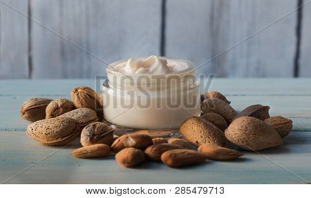 Homemade Facial Cream Of Almond Oil Surrounded By Natural Almonds, N A White Wooden Background