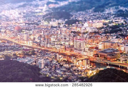 Business Concept, Tilt Shift Effect Modern Cityscape Of Nagasaki Dusk From Mount Inasa, The New Top
