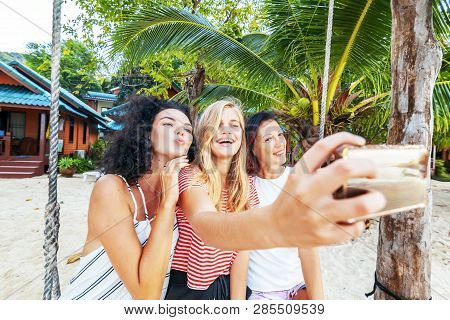 Three Beautiful Slender Happy Girlfriends Students Take Selfie Against The Backdrop Of A Tropical Re