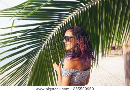 Attractive Young Slim Woman With Multi-colored Hair In Sunglasses On The Background Of Palm Trees, B
