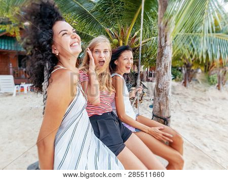 Three Beautiful Slender Happy Girlfriends Students Swing On A Swing Against The Backdrop Of A Tropic