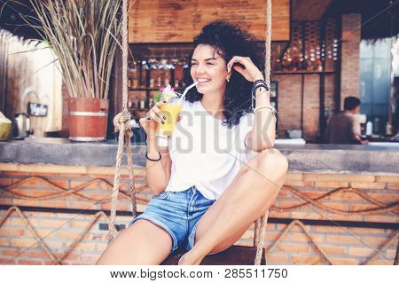Beautiful Young Slim Woman With Dark Curly Hair, In Denim Shorts With Long Tanned Legs, Drinks Fresh