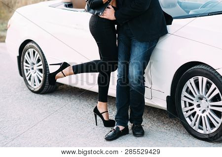 Sympathetic Couple Husband And Wife Spend Time Outside The City And Stand By A White Car