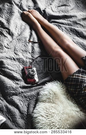 A Girl Rests In A Gray Bed With An Old Camera. Fashion, Style, Vintage A