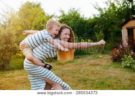 Super Mom, Superman. Happy Caucasian Mother And Son Outdoors In Park On Sunny Spring Day. Young Brun
