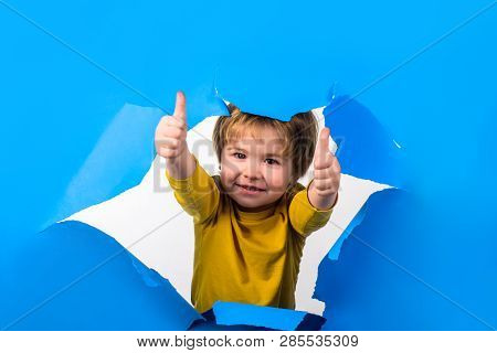 Happy Childhood. Boy Breaking Through Paper Showing Thumbs Up. Happy Kid Giving Thumbs Up Gesture. B