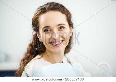 Happy Woman With Braces On Teeth Smiling In Dental Clinic