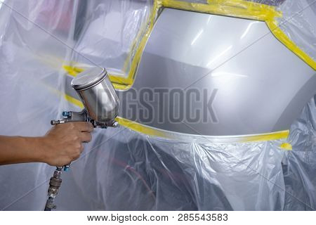 Spray Gun With Paint For Painting A Car ,man With Protective Clothes And Mask Painting Car Using Spr