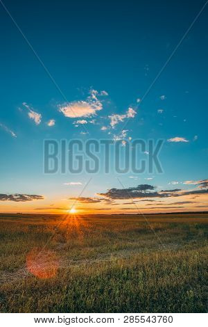 Summer Sunset Sunrise Sky Above Countryside Rural Meadow Landscape. Sun Rising Above Rural Countrysi