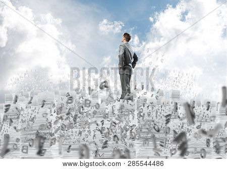Confident Businessman In Suit Standing On Pile Of Documents Among Flying Letters With Cloudly Skysca