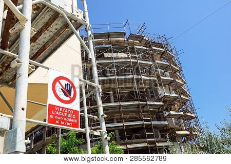No Entry Sign On The Fence In Contruction Site With House Under Construction. Access To Non-professi