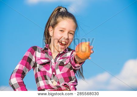 Kid Hold Ripe Apple Sunny Day. Kid Girl With Long Hair Eat Apple Blue Sky Background. Healthy Nutrit