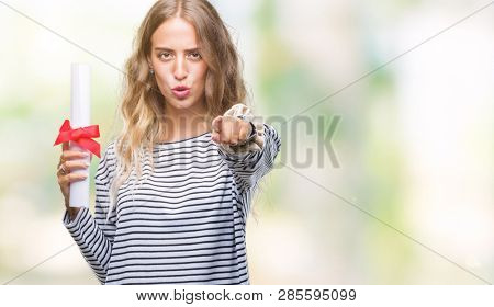 Beautiful young blonde woman holding degree certificate over isolated background pointing with finger to the camera and to you, hand sign, positive and confident gesture from the front