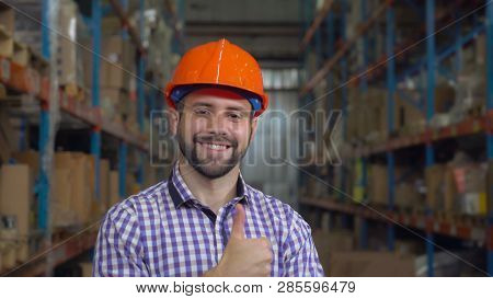 Portrait Worker In Warehouse At Work. Happy Friendly Young Man With Beard Looking At The Camera With