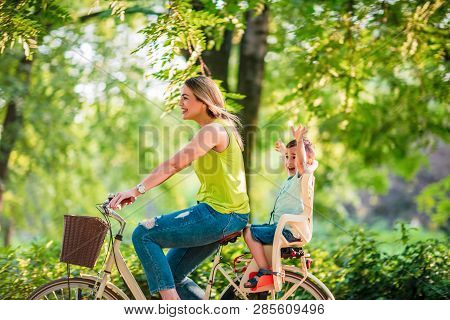 Happy Family. Happy Mother And Son Riding A Bicycle Together Outdoors In A City Park