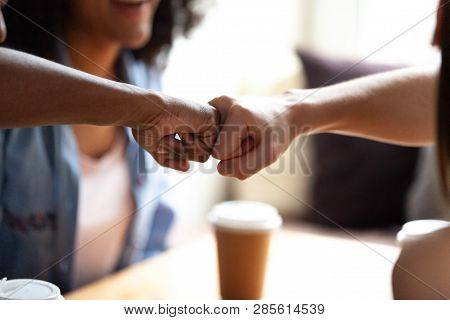Close Up Multiracial Friends Fist Bumping, Celebrate Success In Cafe