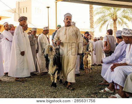 Nizwa, Oman - November 2, 2018: Omani Man Shows A Sheep For Auction At The Nizwa Animal Market