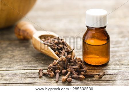 Essential oil of cloves and cloves spice on wooden table.