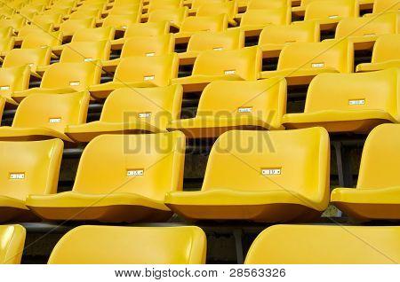 Yellow Empty Plastic Seats At Stadium