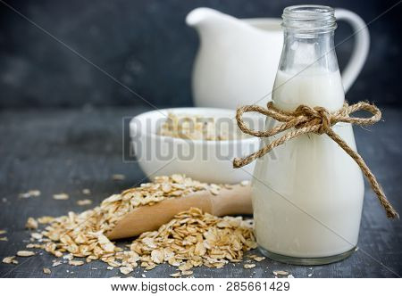 Oat Milk In Glass Jar, Homemade Oat Milk In Bottle And Raw Oat Flakes On Table, Concept Of Vegetaria