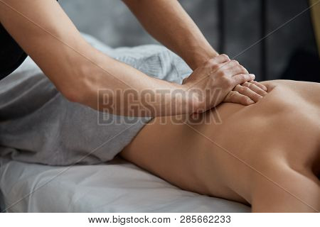 poster of Young handsome man enjoying a back massage. Professional massage therapist is treating a male patient in apartment. Relaxation, beauty, body and face treatment concept. Home massage.