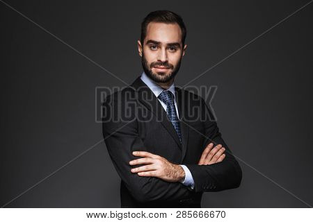 Portrait of a confident handsome businessman wearing suit isolated over black background, arms folded