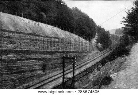 Railway trench having exposed a small section in profile through carboniferous rocks with several small stratifications, vintage engraved illustration. From the Universe and Humanity, 1910.