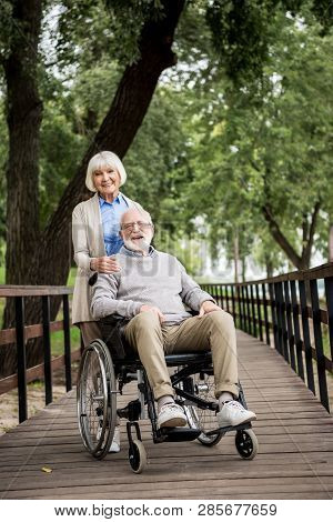 Happy Woman With Smiling Husband In Wheelchair On Wooden Bridge In Park