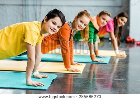 Cheerful Kids Doing Plank Exercise And Looking At Camera