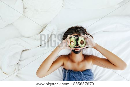 Lifestyle image of 12-14 years old teen girl applying black clay facial mask with avocado. Top view photo of teenage girl wrapped in towel doing organic anti blemish skin care routine.