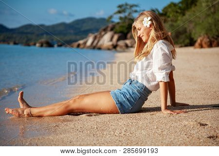 Beautiful Girl In Sea Style Sitting On Sand. Travel And Vacation. Freedom Concept. Sensual Blonde Be