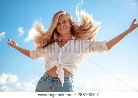 Beautiful Young Blonde Girl With Flowing Hair And Dimples Against The Blue Sky And The Sun, Beauty A