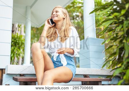 Beautiful Blonde Girl, On The Summer Terrace Of Her House, With A Smartphone In Her Hands, Enjoys Th
