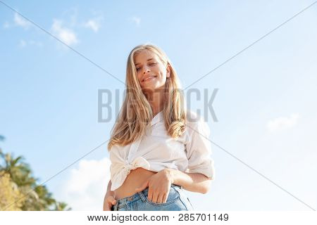 Beautiful Young Blonde Girl With Flowing Hair And Dimples Against The Blue Sky And The Sun, Pretty S